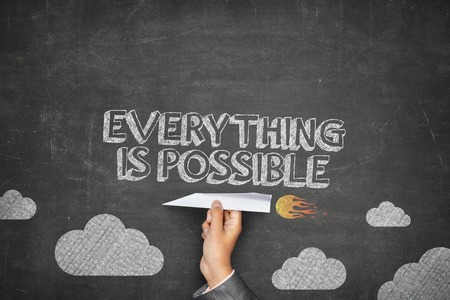 Everything is possible concept on black blackboard with businessman hand holding paper plane