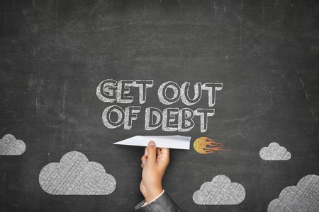 dues: Get out of debt concept on black blackboard with businessman hand holding paper plane