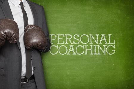 Personal coaching on blackboard with businessman wearing boxing gloves Standard-Bild