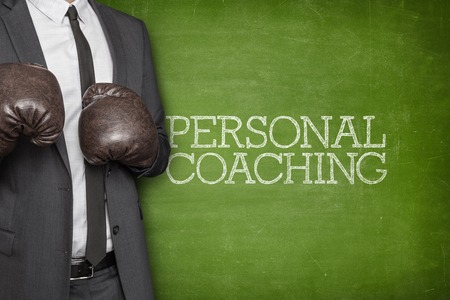 Personal coaching on blackboard with businessman wearing boxing gloves Stock Photo
