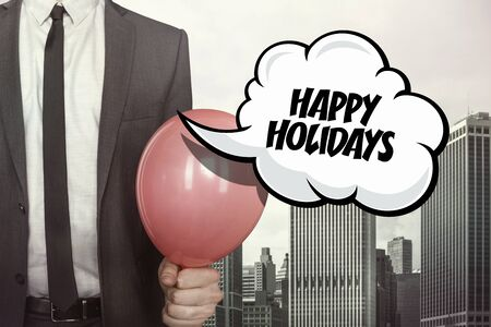jovial: Happy holidays text on speech bubble with businessman holding balloon on cityscape background