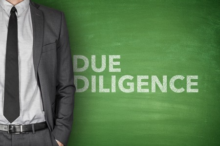 financial agreement: Due diligence on black blackboard with businessman