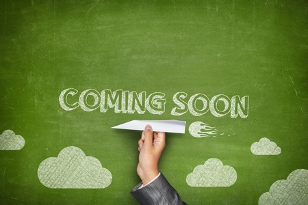 Coming soon concept on green blackboard with businessman hand holding paper plane