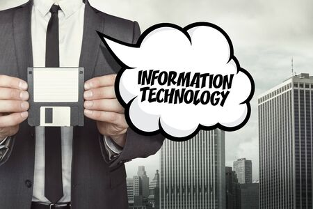 backing: Information technology text on speech bubble with businessman holding diskette on cityscape background Stock Photo