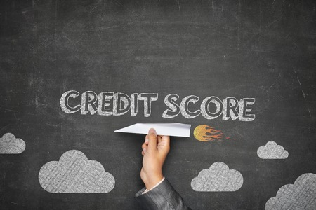 creditworthiness: Credit score concept on black blackboard with businessman hand holding paper plane