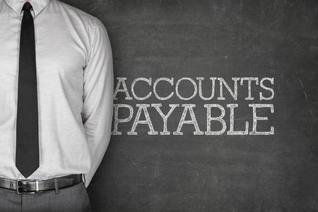 payable: Accounts payable text on blackboard with businessman on side