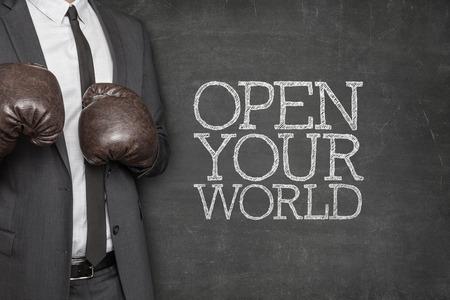 el mundo en tus manos: Abre tu mundo en la pizarra con hombre de negocios con guantes de boxeo
