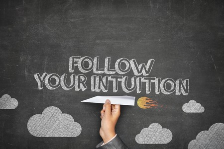 Follow your intuition concept on black blackboard with businessman hand holding paper plane