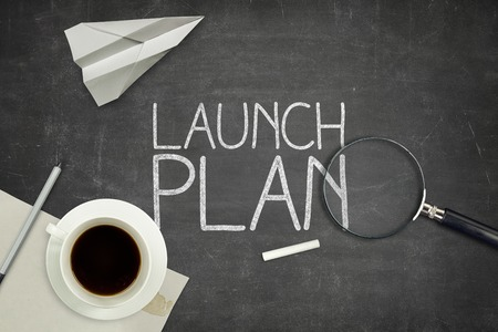 originate: Launch plan concept on black blackboard with coffee cupt and paper plane