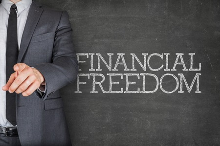 financial freedom: Financial freedom on blackboard with businessman finger pointing
