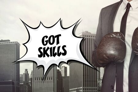 proficiency: Got skills text with businessman wearing boxing gloves on cityscape background