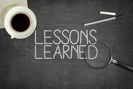 Geleerde lessen concept op zwart bord met koffie cupt en papier vliegtuig Stockfoto