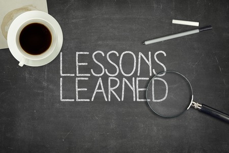 Lessons learned concept on black blackboard with coffee cupt and paper plane