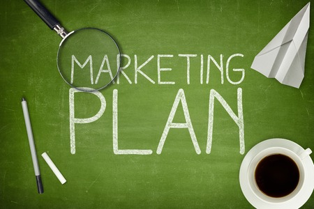 planning: Marketing plan concept on green blackboard with coffee cupt and paper plane