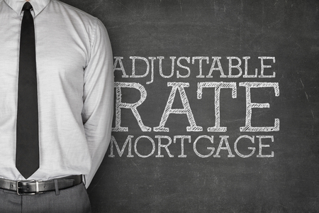 inconstant: Adjustable rate mortgage text on blackboard with businessman on side Stock Photo