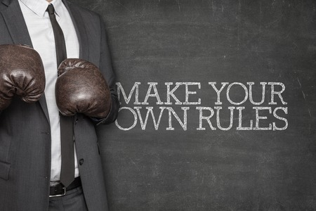 liberated: Make your own rules on blackboard with businessman wearing boxing gloves
