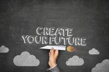 Maak je toekomst concept op zwart bord met zakenman hand houden papier vliegtuig
