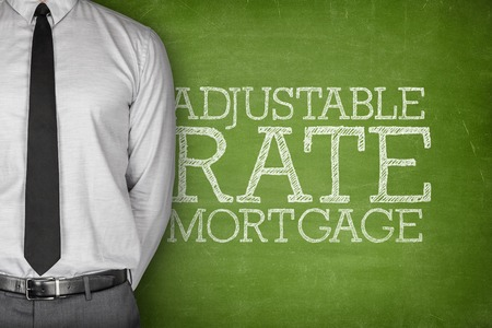 Adjustable rate mortgage text on blackboard with businessman on side Stock Photo