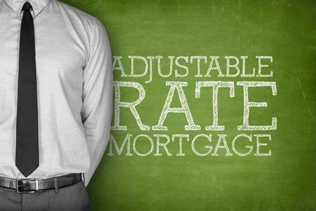 Adjustable rate mortgage text on blackboard with businessman on side Standard-Bild