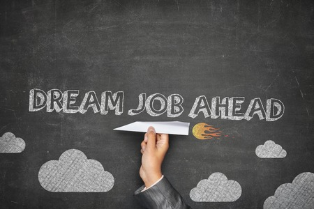 Dream job ahead concept on black blackboard with businessman hand holding paper plane