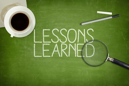 knowledgeable: Lessons learned concept on green blackboard with coffee cupt and paper plane