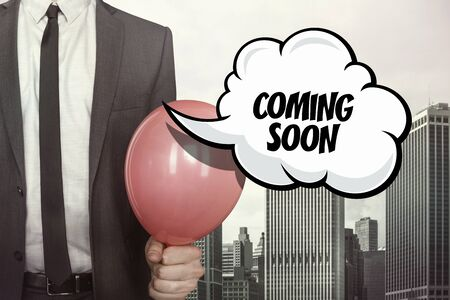 approaching: Coming soon text on speech bubble with businessman holding balloon on cityscape background Stock Photo