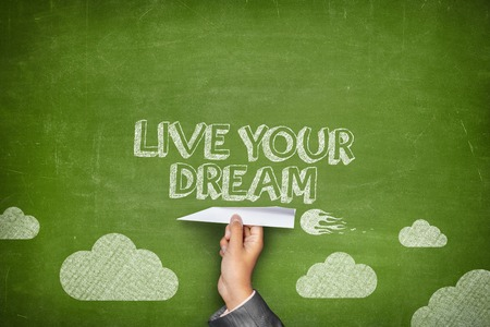 Live your dream concept on green blackboard with businessman hand holding paper plane Stock Photo