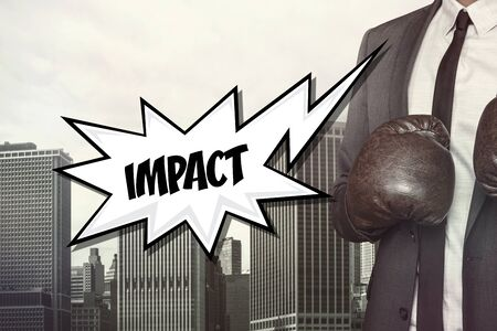 impact: Impact text with businessman wearing boxing gloves on cityscape background Stock Photo
