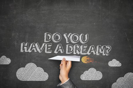 Do you have a dream concept on black blackboard with businessman hand holding paper plane