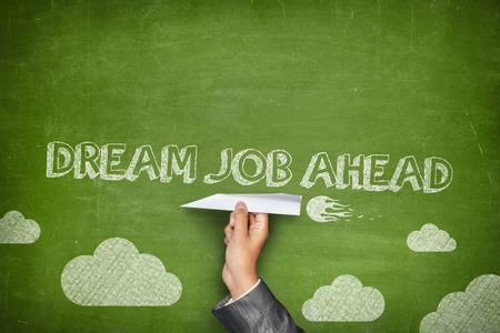 Dream job ahead concept on green blackboard with businessman hand holding paper plane