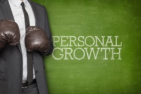 persoonlijke groei: Persoonlijke groei op bord met zakenman dragen bokshandschoenen Stockfoto