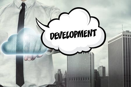 growth enhancement: Development text on cloud computing theme with businessman on cityscape background