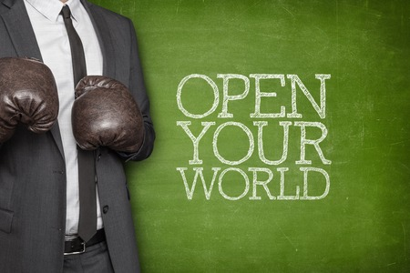 black professional: Open your world on blackboard with businessman wearing boxing gloves Stock Photo