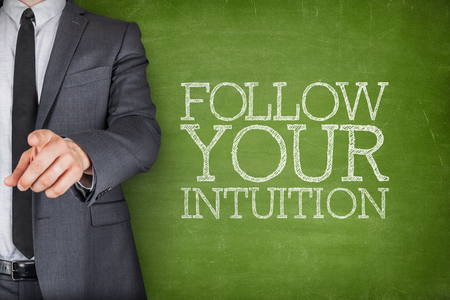 intuition: Follow your intuition on blackboard with businessman finger pointing