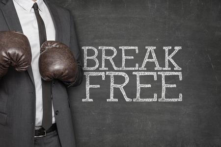 break free: Break free on blackboard with businessman wearing boxing gloves