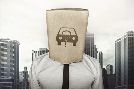 puzzlement: Buy a car concept on brown paper bag which businessman has on head on cityscape background