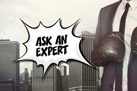 knowledgeable: Ask an expert text with businessman wearing boxing gloves on cityscape background Stock Photo