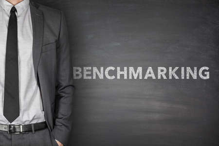 benchmarking: Benchmarking text on black blackboard with businessman
