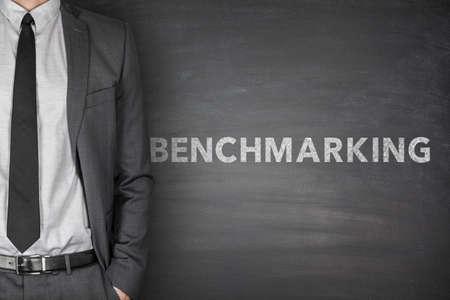 benchmarking: Benchmarking text on black blackboard with businessman