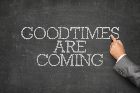 good times: Good times are coming text on blackboard with businessman hand pointing Stock Photo