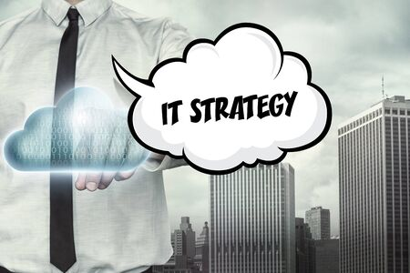 IT strategy text on cloud computing theme with businessman on cityscape background Stock Photo