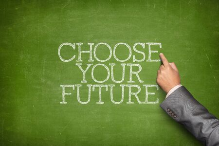 forthcoming: Choose your future text on blackboard with businessman hand pointing Stock Photo