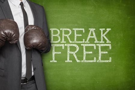 unrestricted: Break free on blackboard with businessman wearing boxing gloves
