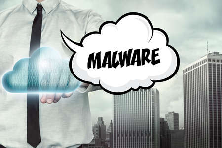 malicious software: Malware text on cloud computing theme with businessman on cityscape background Stock Photo