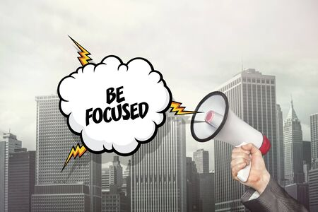focused: Be focused text on speech bubble and businessman hand holding megaphone on city background