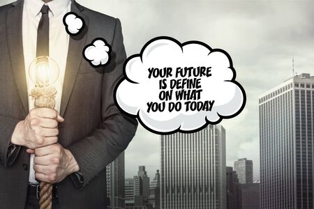 define: Your future is define on what you do today text on speech bubble with businessman holding lamp on city background Stock Photo