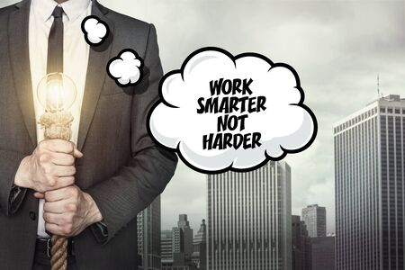 harder: Work smarter not harder text on speech bubble with businessman holding lamp on city background