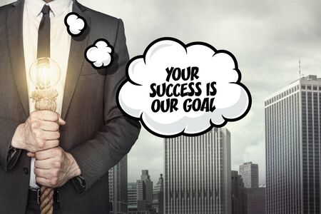 succes: Your succes is our goal text on speech bubble with businessman holding lamp on city background