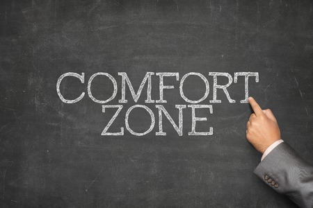 reassurance: Comfort zone text on blackboard with businessman hand pointing