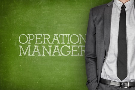 specialized job: Operations manager on blackboard with businessman in a suit on side Stock Photo